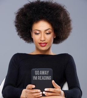 """A black woman reading an ereader. The ereader has a signs saying """"go away. I'm reading"""""""