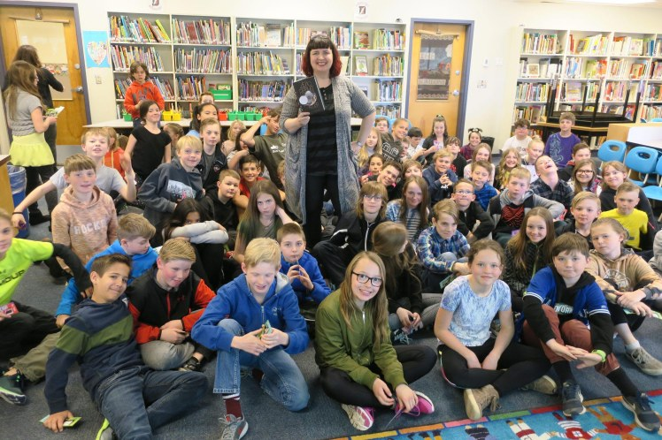 The author with grade 5 and 6 students in their school library